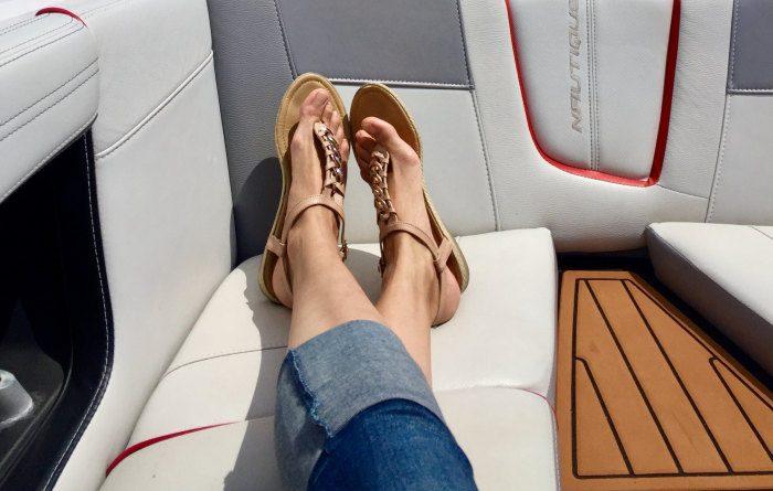 femeie care sta intinsa pe o bancheta si poarta sandale cu talpa plata