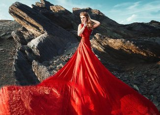 femeie imbracata in rochie rosie la tarmul marii