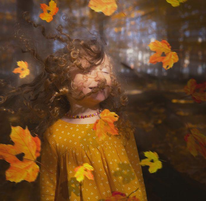 Fetiță care se joacă cu frunze