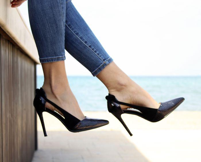 femeie in blugi, incaltata cu pantofi cu toc negri