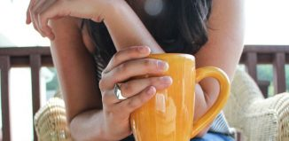femeie care tine in mana o cana cu cafea
