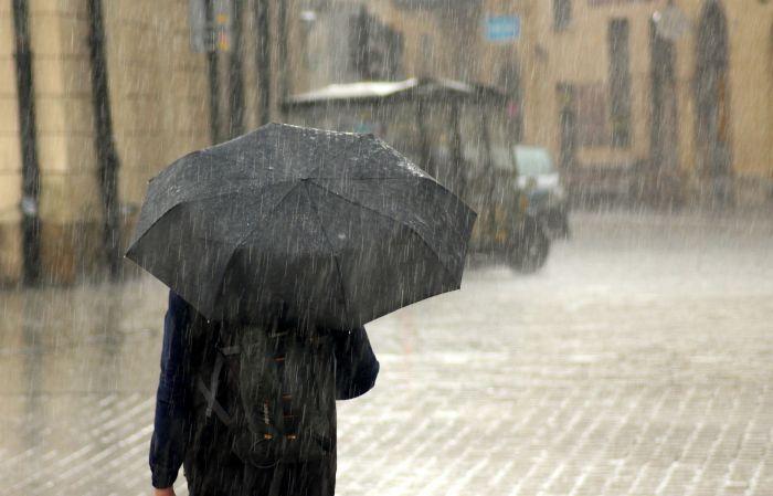 persoana care merge prin ploaie cu umbrela