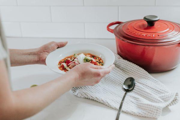 femeie care tine in mana o farfurie cu supa