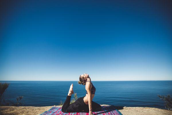 femeie care face yoga pe plaja