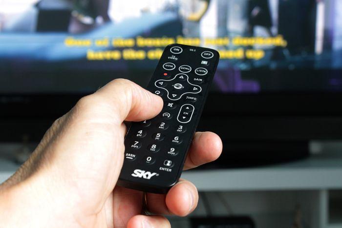 persoana care butoneaza o telecomanda tv