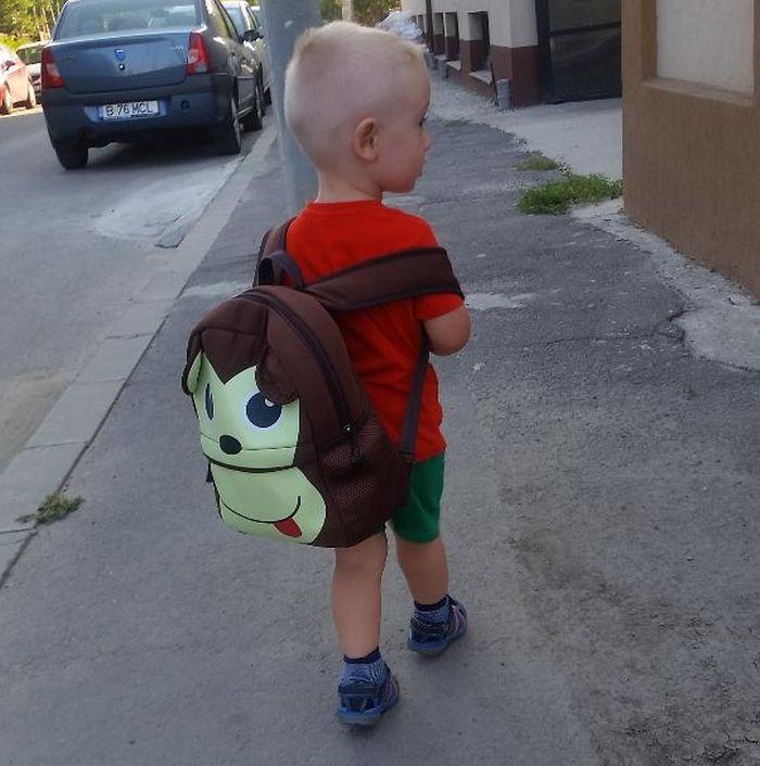Copil mic cu ghiozdanul in spate pe strada