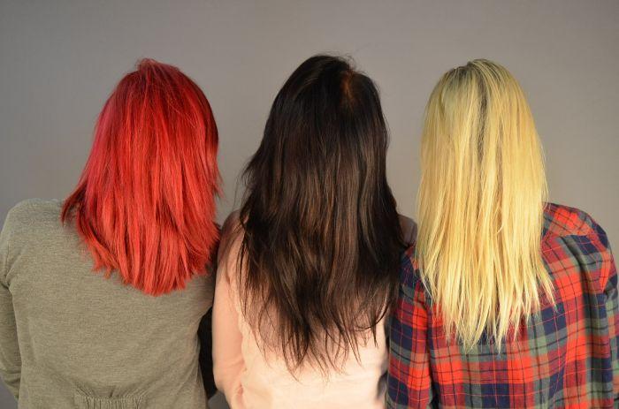 Trei femei care stau cu spatele și au parul vopsit roscat, brunet și blond