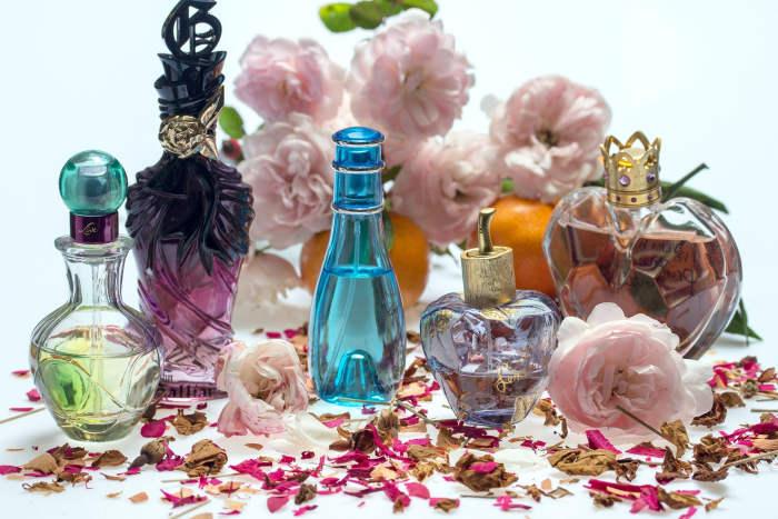 Sticlute de parfum colorate, cu iz floral langa un buchet de trandafri
