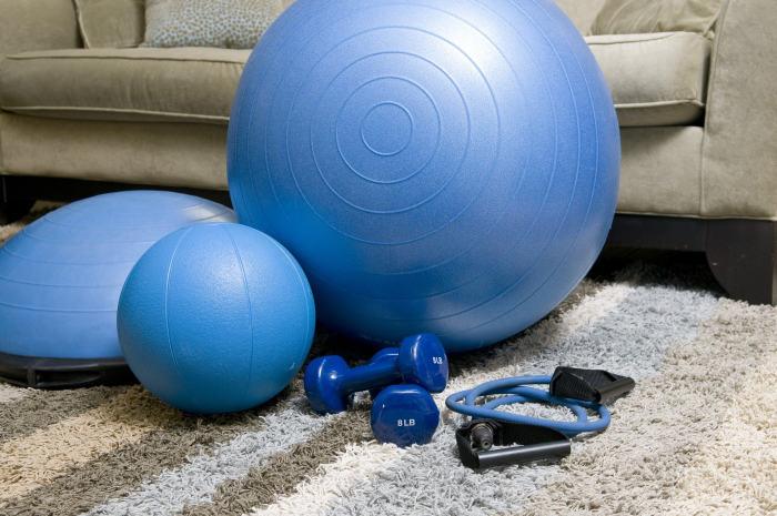 Gantere, extensor și mingii albastre de fitness asezate pe covor in living