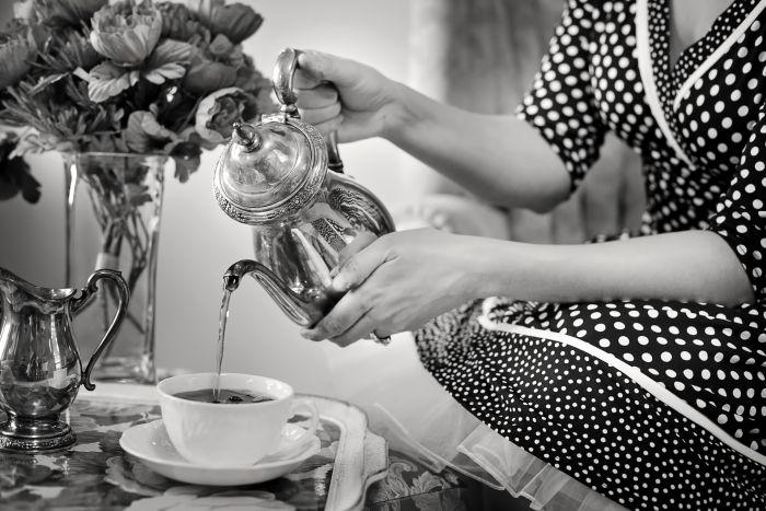 Femeie îmbrăcată în rochie vintage, care toarnă ceai într-o ceașcă